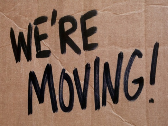 cardboard We're Moving sign with black letters